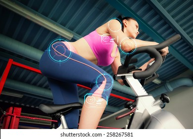 Determined young woman working out at class against fitness interface