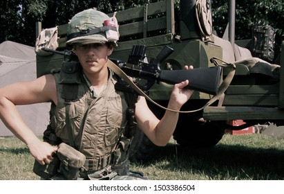 Detling Kent August 2019. Zach a Vietnam War reenactor wears the period uniform of a US Rifleman he kneels down holding an M16 Rifle over his shoulder at a re-enactment event.