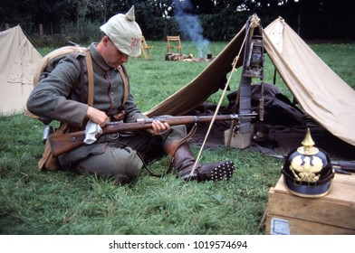 Detling Kent England 2002. A reenactor of WW1 wears the uniform of a WW1 German Infantryman he wears a period spiked helmet and holds a bolt action rifle while smoke rises from the camp scene behind.