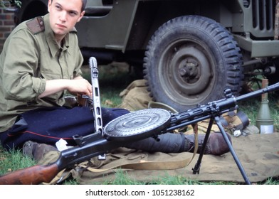 Detling Kent England 2003. An unidentified WW2 reenactor wears the uniform of a Russian DP Machine Gunner he sits cleaning a PPSH machine gun at a re-enactment of the defence of Brest Fortress 1941.