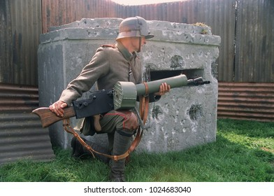 Detling Kent England 2017. A reenactor in the period uniform of a WW1 German machine gunner sat in front of a concrete bunker and holding a machinegun at a re enactment event of WW1.