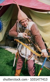 Detling Kent England 2017. A reenactor of the ancient Greek period dressed as a Scythian Archer holding a bow in front of a tent at a reenactment event.