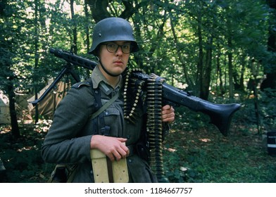 Detling Kent UK August 2018. A young WW2 reenactor wears the period clothing of a German Mg42 gunner he stands with a MG42 machine gun over his shoulder at a re-enactment event.