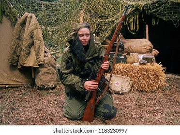 Detling Kent UK July 2018. A female reenactor of the 2nd Guards Division wears the uniform of a WW2 Soviet sniper she kneels holding a Moisin Nagent rifle at a re-enactment event.