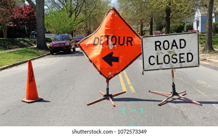 DETOUR and ROAD CLOSED signs on residential neighborhood street.
