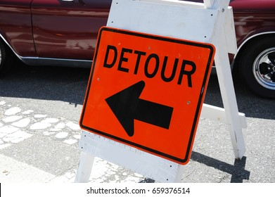 detour sign on road in front of car