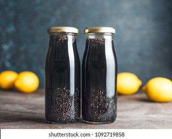Detox activated charcoal black chia water or lemonade with lemon. Two bottle with black chia infused water. Detox drink idea and recipe. Vegan food and drink