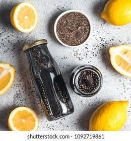 Detox activated charcoal black chia water or lemonade with lemon. Two bottle with black chia infused water. Detox drink idea and recipe. Vegan food and drink. Top view.