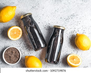 Detox activated charcoal black chia water or lemonade with lemon. Two bottle with black chia infused water. Detox drink idea and recipe. Vegan food and drink. Top view. Copy space for text.