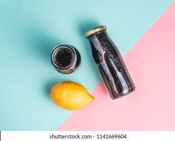 Detox activated charcoal black chia water or lemonade with lemon on colorful blue and pink background.Two bottle with black chia infused water.Detox drink idea and recipe.Vegan food and drink.Top view