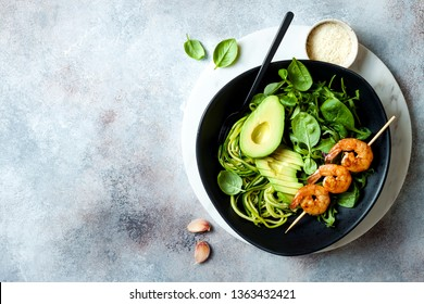 Detox Buddha bowl with avocado, spinach, greens, zucchini noodles, grilled shrimps and pesto sauce. Vegetarian vegetable low carb lunch bowl.