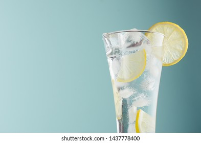Detox citrus drink with lemon slices, ice cubes, sparkling water in misted glass in modern mint color background, closeup, edge, top, half.