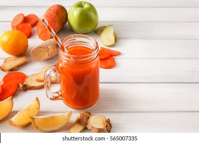Detox cleanse drink, vegetable smoothie ingredients. Natural, organic healthy juice in glass jar for weight loss diet or fasting day. Carrot, apple, ginger and lemon mix on white wood with copy space
