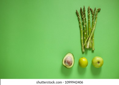 Detox concept, healthy green vegetable smoothie ingredients on green background. Vegetarian food.