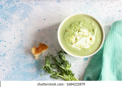 Detox cream soup of green vegetables (broccoli, green peas, spinach) served with cream, lemon zest and micro greens on grey concrete background. Clean eating, healthy food concept. Top view.