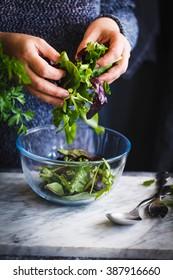 Detox and dieting salad. Hand preparing healthy vegetable salad. rustic blue style.