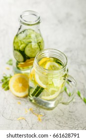 Detox drink with cucumber, lemon and celery in a glass jar and bottle on a white background