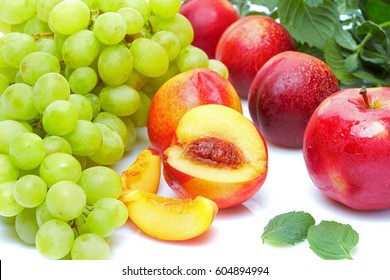 Detox food and drink healthy diet: Green and orange fruits vegetables and juices.  Sweet grapes peaches apples and aromatic mint. Top view. Isolated on white.