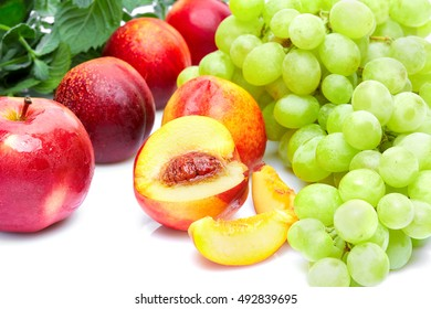 Detox food & drink healthy lifestyle concept: An aromatic colorful tasty delicious fruits vegetables & herbs. Apple, peach, grapes & mint. Top view. Isolated on white.