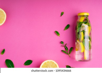 Detox fruit infused water, citrus fruits and mint leaves on pink background. Flat lay summer background with summer drink. Top view. Copy space