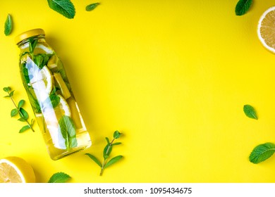 Detox fruit infused water, citrus fruits and mint leaves on yellow background. Flat lay summer background with summer drink. Top view. Copy space