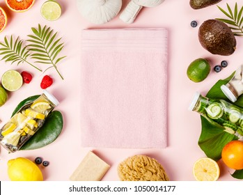 Detox fruit infused water, tropical fruits, leaves and SPA settings on pink pastel background. Top view, flat lay, space for text