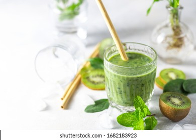 Detox green smoothie - kiwi, spinach and matcha on a light grey slate, stone or concrete background. Selective focus, copy space. Top view.