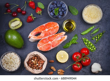 Detox healthy food concept with salmon fish, vegetables, fruits and ingredients for cooking. Selection of healthy and good for heart food. View from above, top studio shot