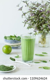 Detox, healthy green smoothie in a glass  with matcha and spinach