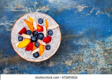 Detox and healthy superfoods breakfast bowl concept. Vegan coconut milk chia seeds pudding over blue stone table with various fruits and blueberries. Overhead, top view, flat lay.