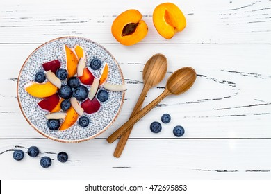 Detox and healthy superfoods breakfast bowl concept. Vegan coconut milk chia seeds pudding over rustic table with various fruits and blueberries. Overhead, top view, flat lay.