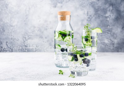 Detox infused flavored water with blueberry, cucumber and thyme on white background. Refreshing summer homemade cocktail
