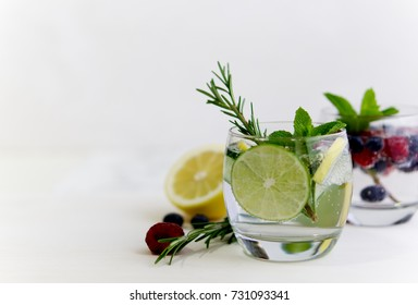 Detox infused flavored water with lemon, lime, blueberry, raspberry, rosemary, cucumber and mint on white wooden background. Refreshing summer homemade cocktail
