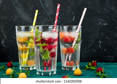 Detox infused flavored water with three color raspberry - red, orange, yellow on green background. Refreshing summer homemade cocktail