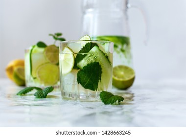 Detox infused water with cucumber, mint and lime in drink in transparent glass. Detox drink, health care