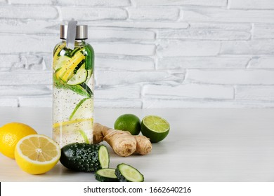 Detox infused water with lemon, lime, ginger and cucumber in a glass sport bottle on white wooden background over brick wall. Detoxification. Healthy eating concept.