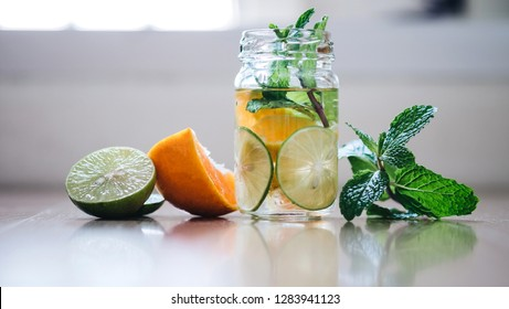 Detox Infused Water with Lemon, Orange, Peppermint, blurred background