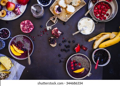Detox smoothie bowl concept. High angle view of prepared colorful breakfast chia smoothies over dark stone table with various tropical fruits. Healthy breakfast bowl concept.