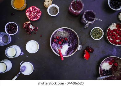 Detox smoothie bowl concept. High angle view of prepared colorful breakfast chia coconut smoothies over dark  table with various tropical fruits and jars of yogurt. Healthy breakfast bowl concept.