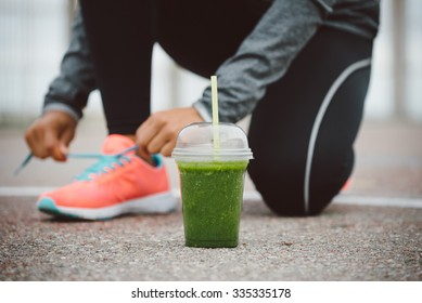 Detox smoothie drink and running footwear close up. City outdoor workout and fitness healthy nutrition concept.  Female athlete tying sport shoes laces before training.