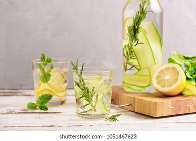 Detox Water Flavored with Sliced Lemon, Cucumber, Rosemary and Fresh Sprigs of Mint. Copy Space