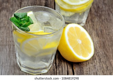 Detox water with fresh lemon and mint on wood table