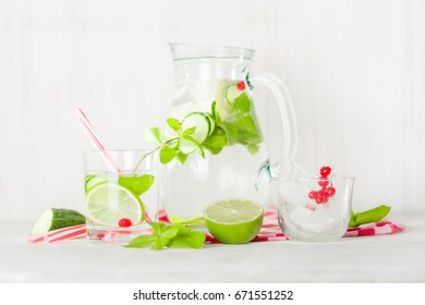 Detox water in a glass jug and a glass. Berries and lime, red and green. Fresh mint leaves. Bright white background.