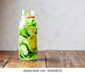 Detox Water Infused with Sliced Lemon, Cucumber and Sprigs of Mint. Copy Space on the Right.