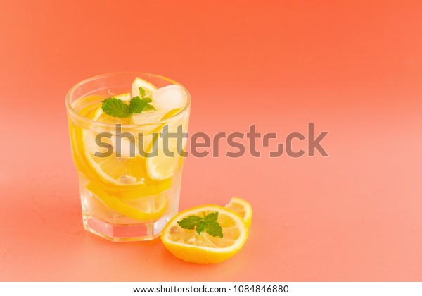Detox Water with lemon in a glass on an orange background.