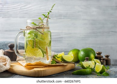 Detox water with lime, thyme and mint  in a mason jar against a rustic stone background