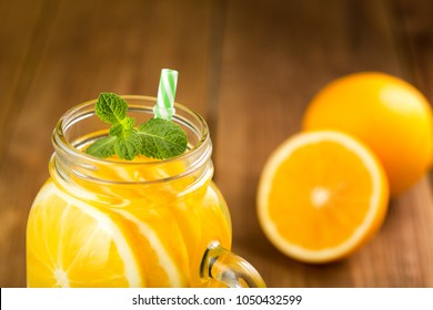 Detox water with orange slices in a glass jar with a handle clos