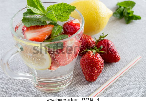 Detox water with strawberry,lemon and mint in the glass on the grey background