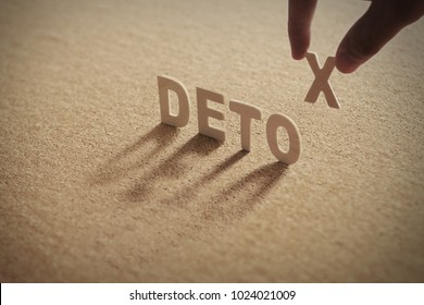 DETOX wood word on compressed or corkboard with human's finger at X letter.