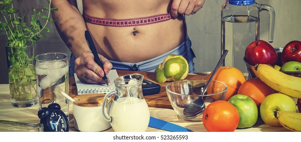 Detox. Young girl measures the waist and uses proper nutrition. Detox drinks, ingredients, dumbbells. Concept: healthy lifestyle.